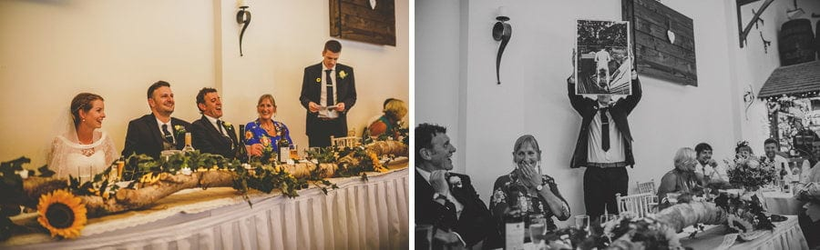 The groom's brother holds up a large photograph of the groom during his wedding speech at Yarlington barn in Somerset