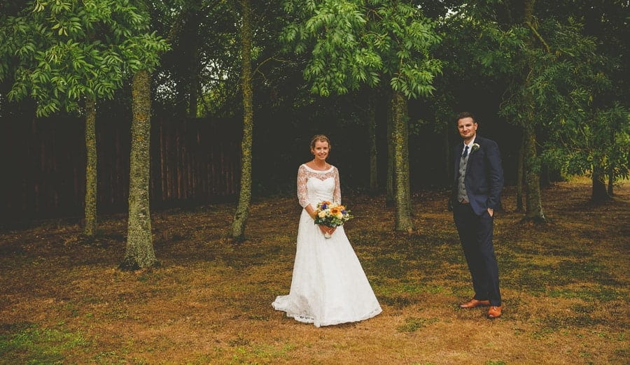 The bride and groom pose for a photograph in the gardens at Yarlington barn in Somerset
