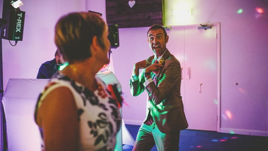 A wedding guest dancing with his wife makes a gesture to her on the dancefloor at Yarlington barn