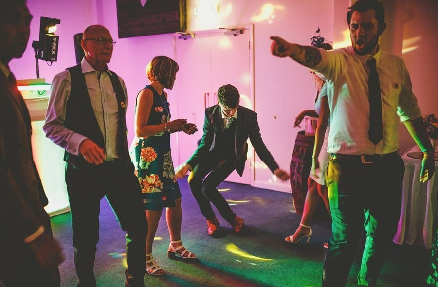 A wedding guest dancing as other wedding guests stand and watch him at Yarlington barn