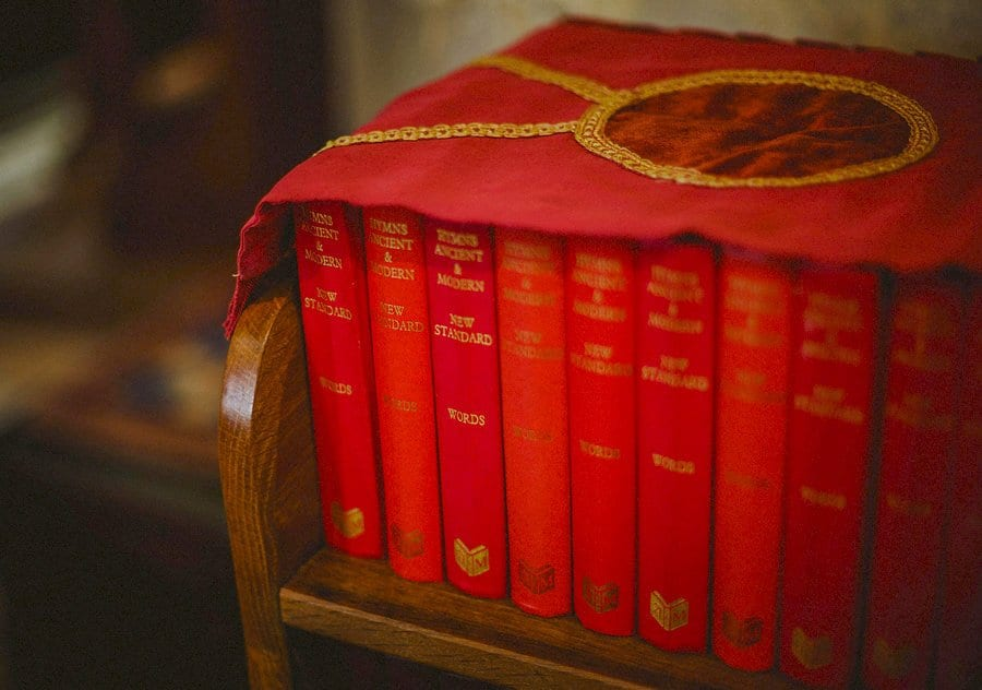 Church hymn books rest on a shelf