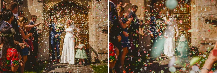 Wedding petals shower the bride and groom outside Batcombe church