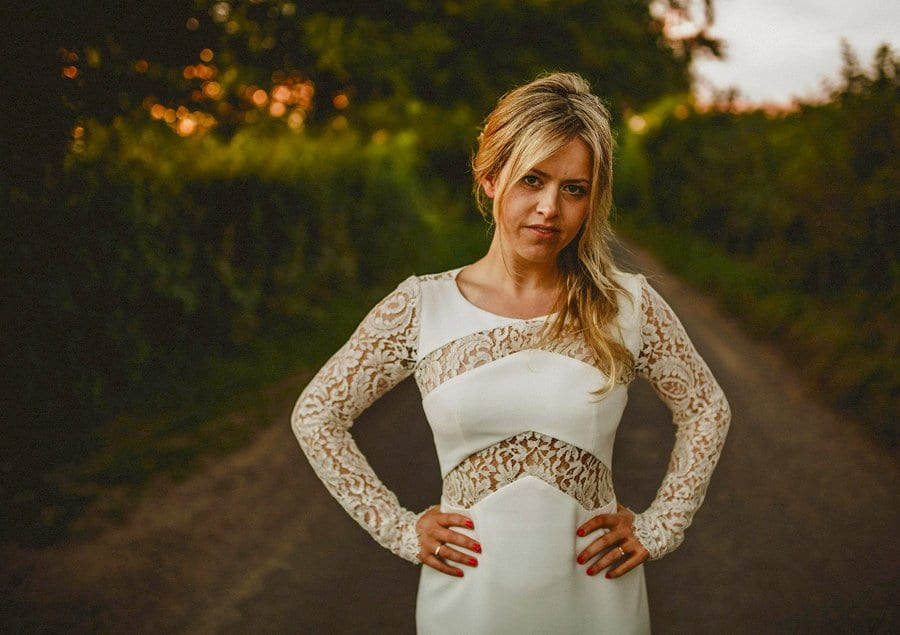 The bride poses for a photograph along a country lane outside Penny Square Barn