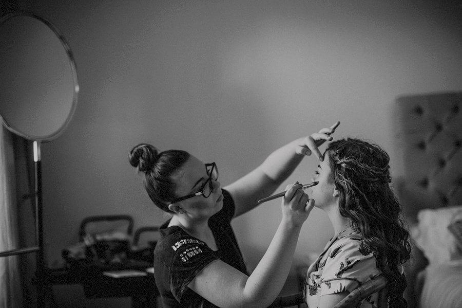 A make up artist applying make up to a bridesmaid