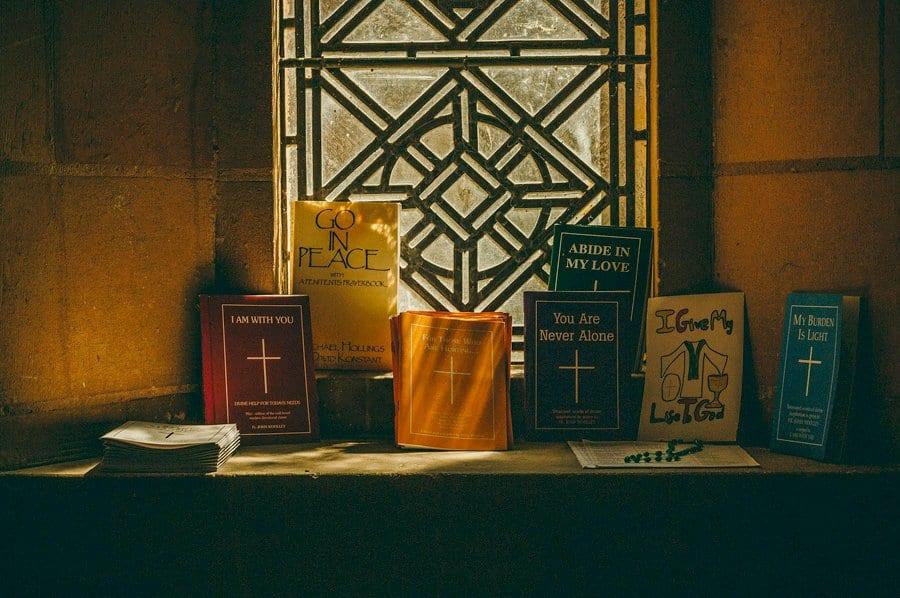 Wedding hymn books lay on a stone window ledge