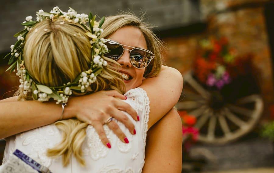 A wedding guest congratulates the bride in the courtyard