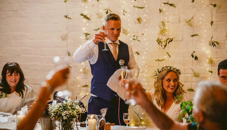 The groom raises his glass with friends and family as he makes a toast to his wife in the barn