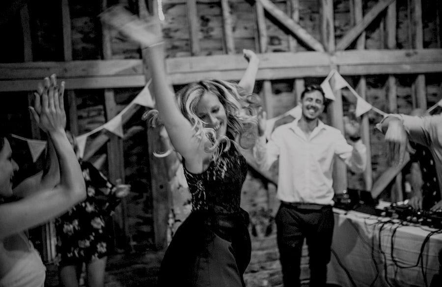 A lady throws her arms up in the air and dances at Over Barn