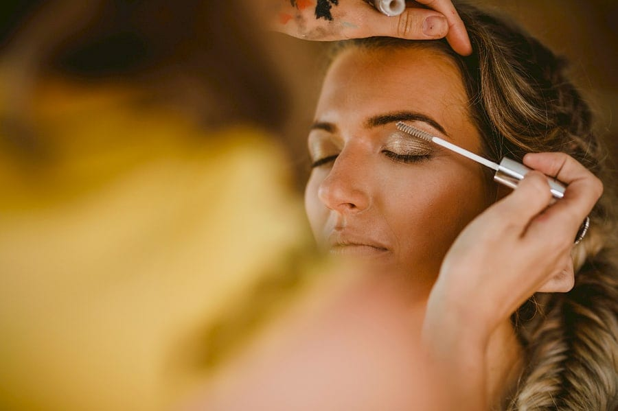 A makeup artist carefully applies mascara onto the eyebrows of one of the bridesmaids in the cottage at Yurt retreat