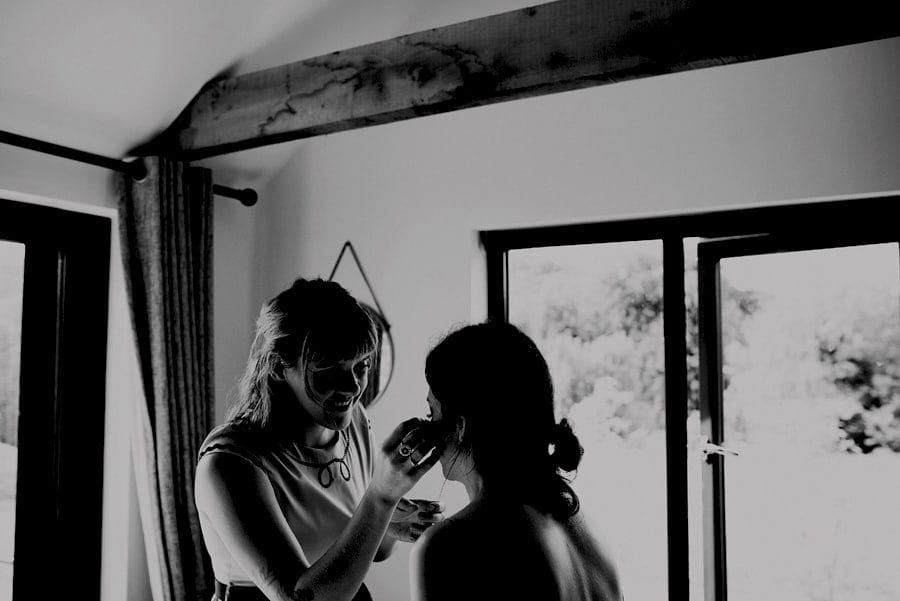 The makeup artist applies mascara to the brides face in the cottage at Yurt retreat in Crewkerne, Somerset