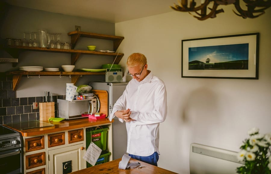 The groom puts on his cufflinks in the kitchen of the cottage
