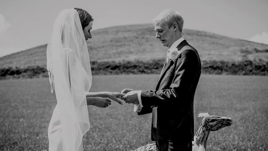 The groom places a ring on the finger of the bride during the outdoor wedding ceremony