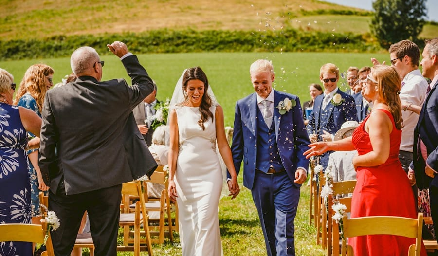 The bride and groom walk down the aisle of the outdoor ceremony as guests throw confetti in the air