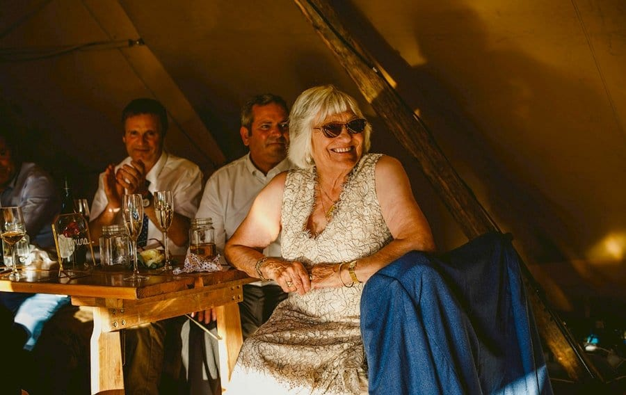 The brides grandmother laughs at one of the speeches in the tipi