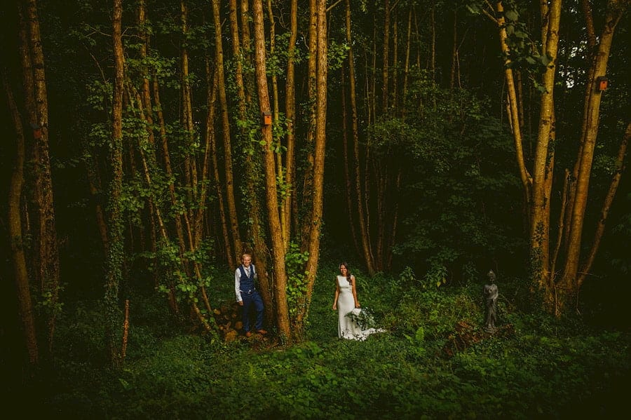 The bride and groom pose for a photograph as they stand next to each other in the woods at the Yurt Retreat in Crewkerne, Somerset