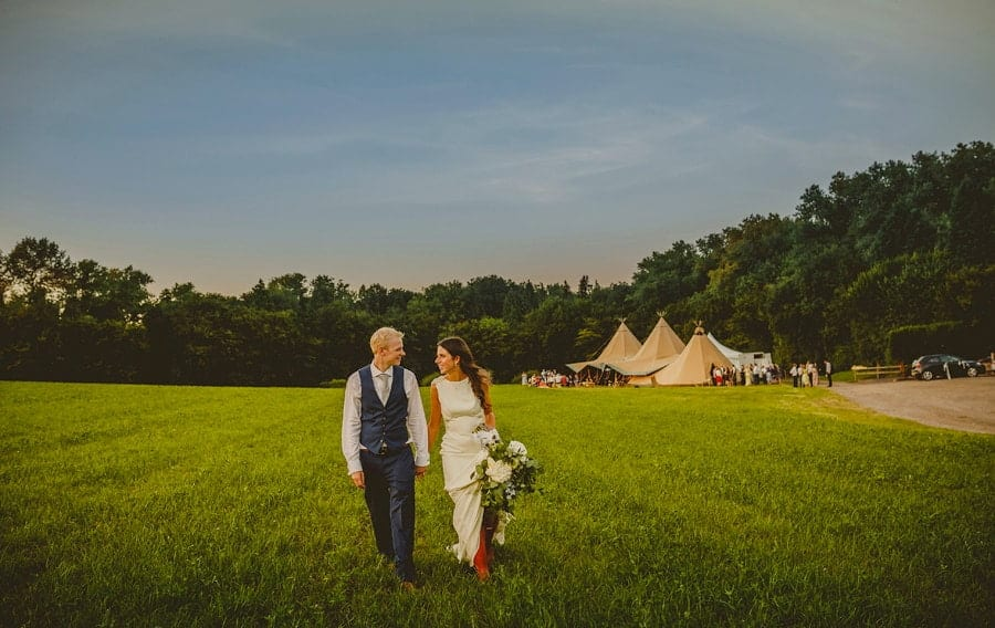 The bride and groom look at each other and walk hand in hand across the field at Yurt Retreat