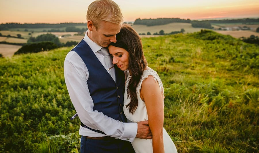 The bride puts her head on the grooms chest and closes her eyes on top of the hill at yurt retreat in Crewkerne, Somerset