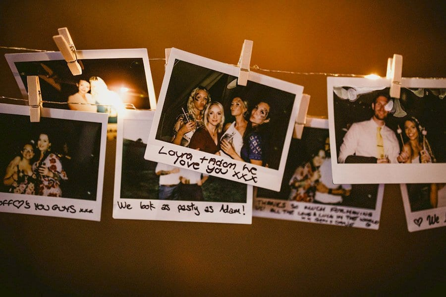 Polaroid photographs of the wedding day hang from string in the tipi at yurt retreat