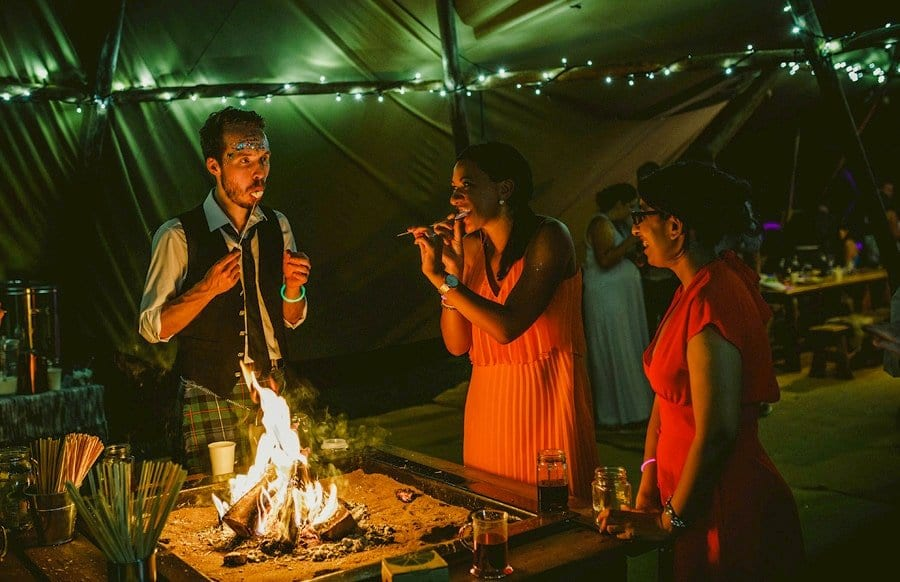 Wedding guests toast marsh mellows over an open lit fire in the tipi