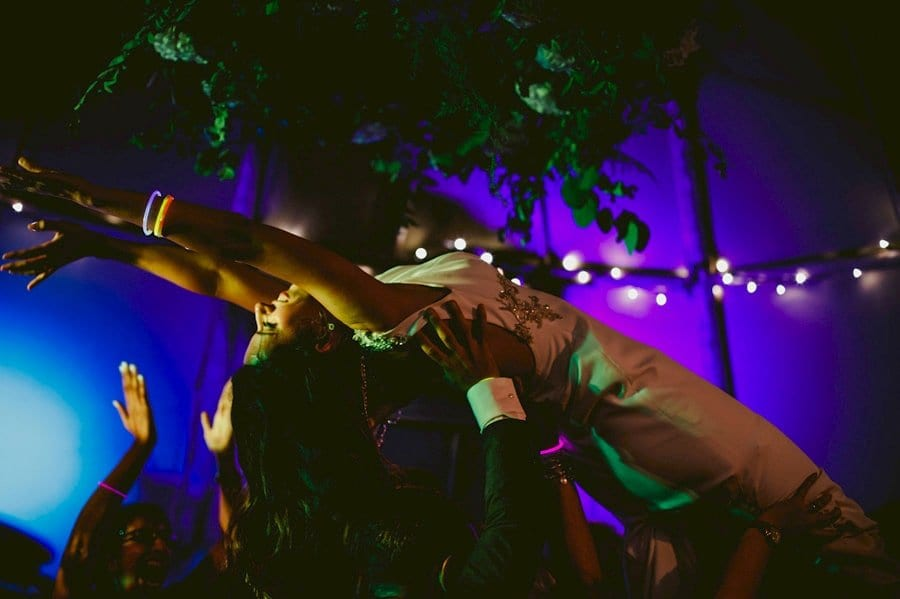 Wedding guests raise the bride in the air on the dancefloor in the tipi