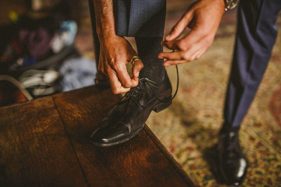 The groom ties his shoe laces in one of the rooms at Abbey House Gardens in Malmesbury