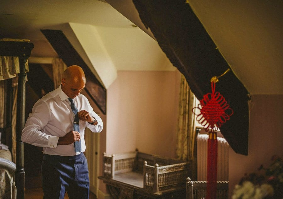 The groom looks down and straightens his tie in a bedroom at Abbey House Gardens