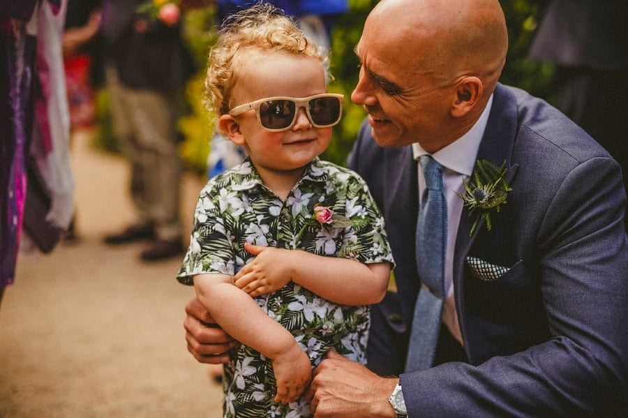 The groom smiles at his son wearing sunglasses in the gardens outside Abbey House