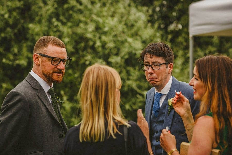 A wedding guest pulls a face as he listens to another wedding guest