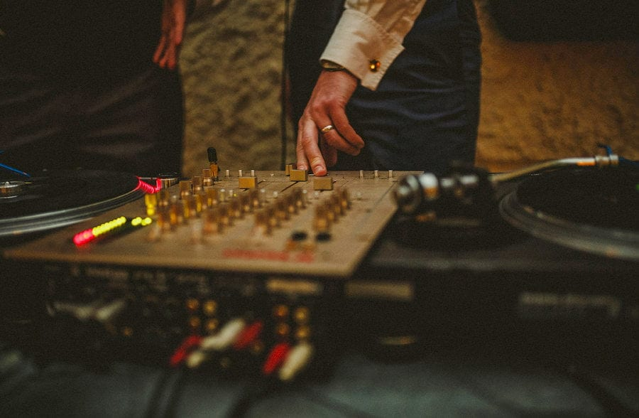 The DJ places his fingers on the mixing desk