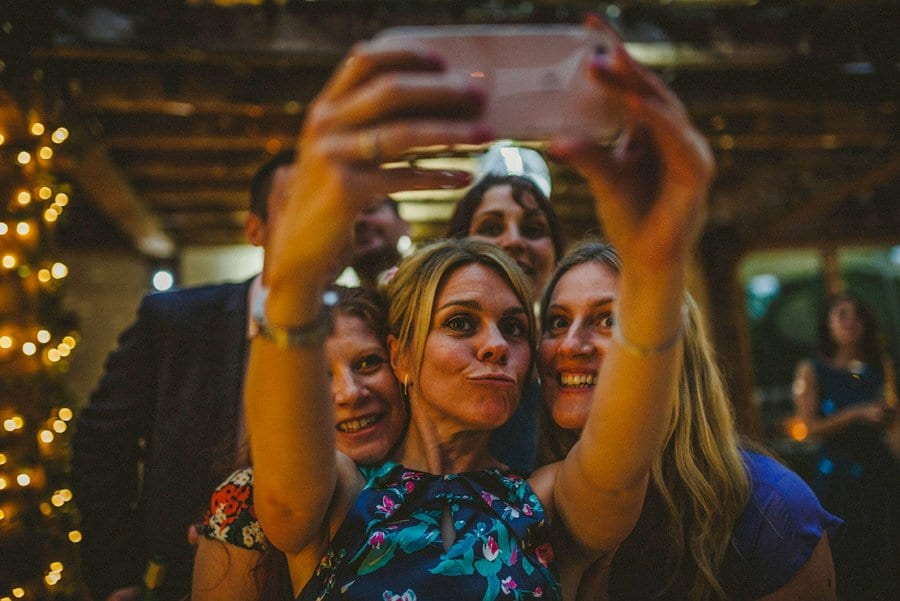 A lady holds up a mobile phone and takes a photograph of herself and her friends on the dancefloor