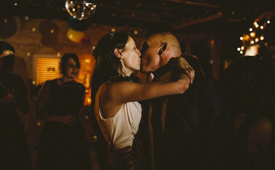 The bride kisses the groom on the dancefloor