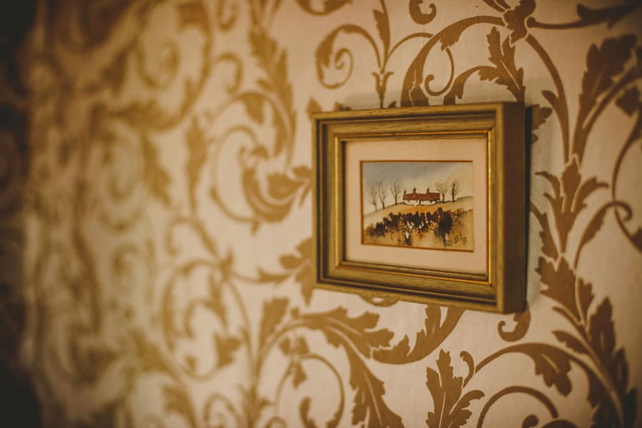 A framed oil painting hangs from a wall in a cottage