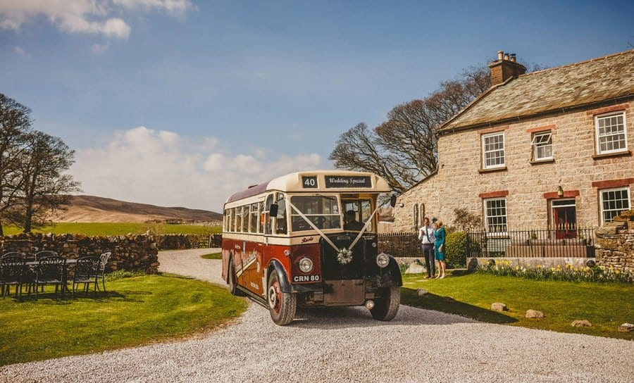 The wedding bus arrives outside the cottage