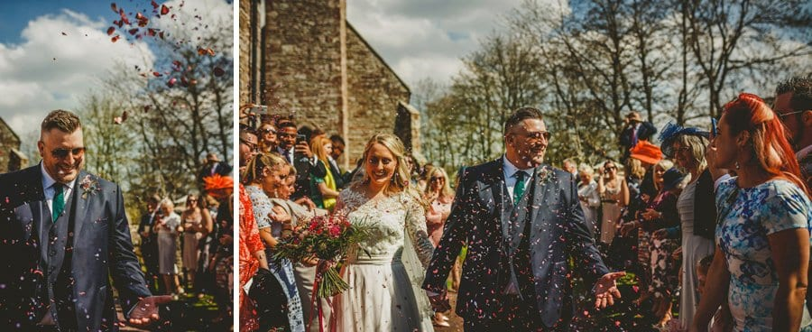 The bride and groom walk out of the church and are showered in confetti