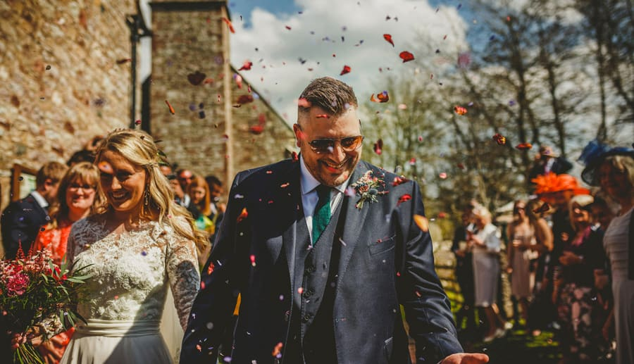 The groom catches confetti that has been thrown over him by wedding guests outside the Church