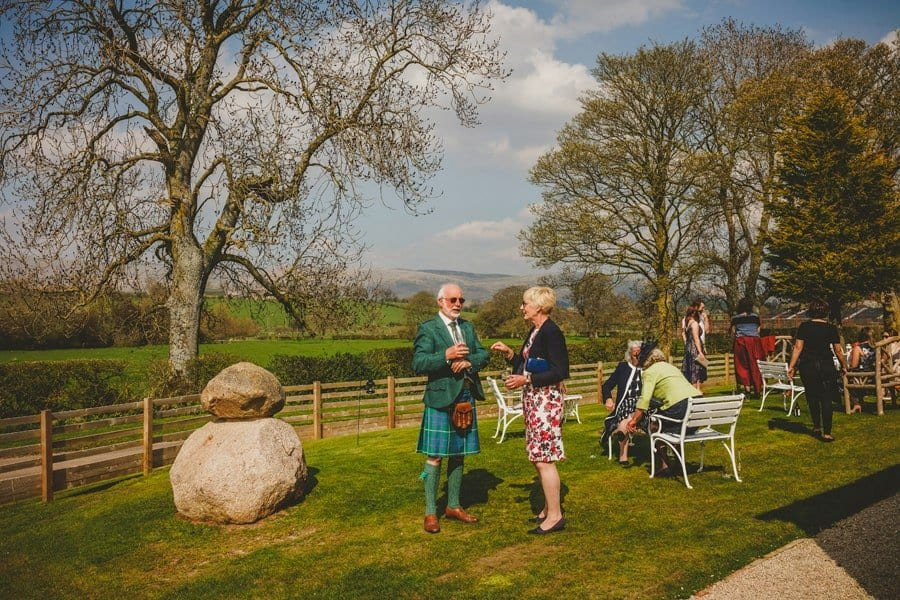 Wedding guests drink champagne and chat to one another in the garden at Eden Barn