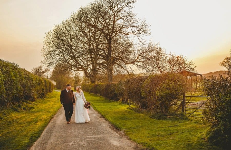 The bride and groom walk along the lane outside Eden Barn as the sunsets