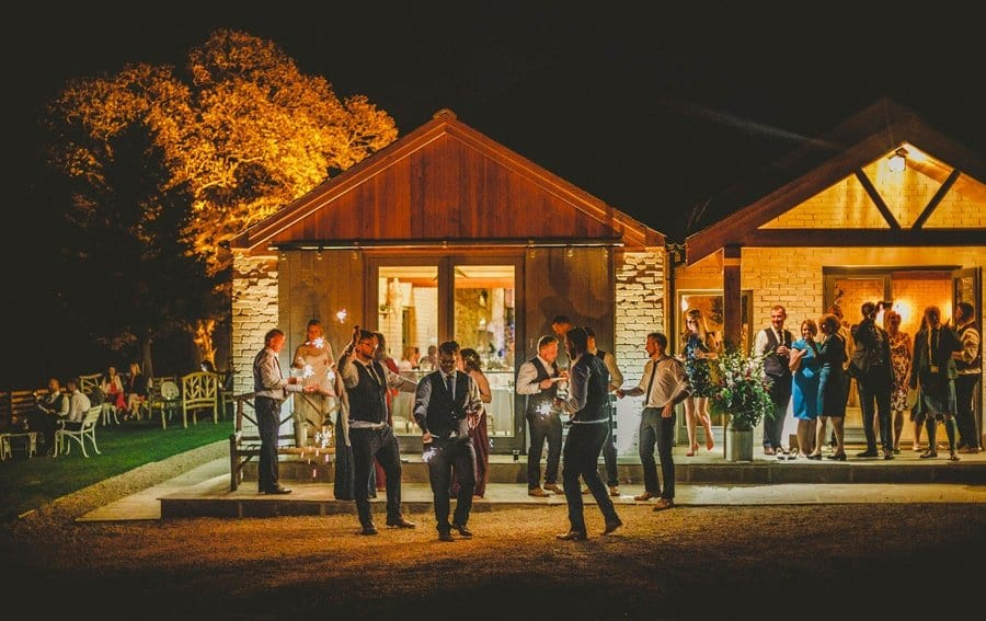 Wedding guests light sparklers outside Eden Barn in the evening
