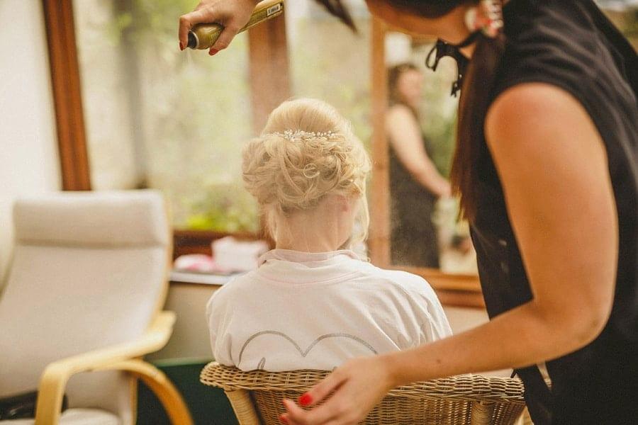 A lady sprays hair spray on the bridesmaids hair