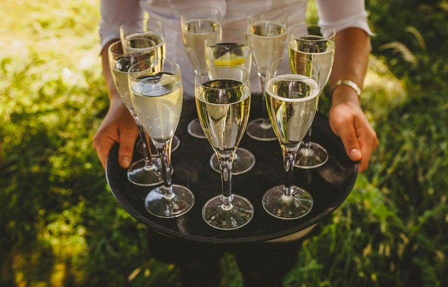 A waitress holds a tray full of flutes filled with champagne
