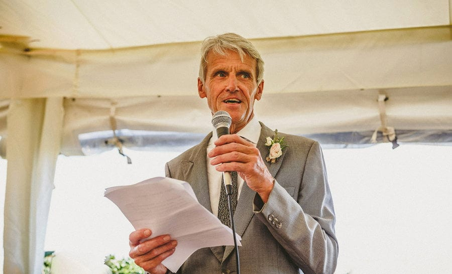 The brides father delivers his speech to the wedding party in the marquee