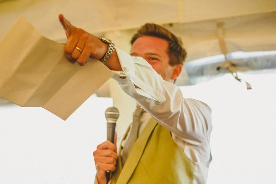 The groom points to an usher as he delivers his wedding speech in the marquee