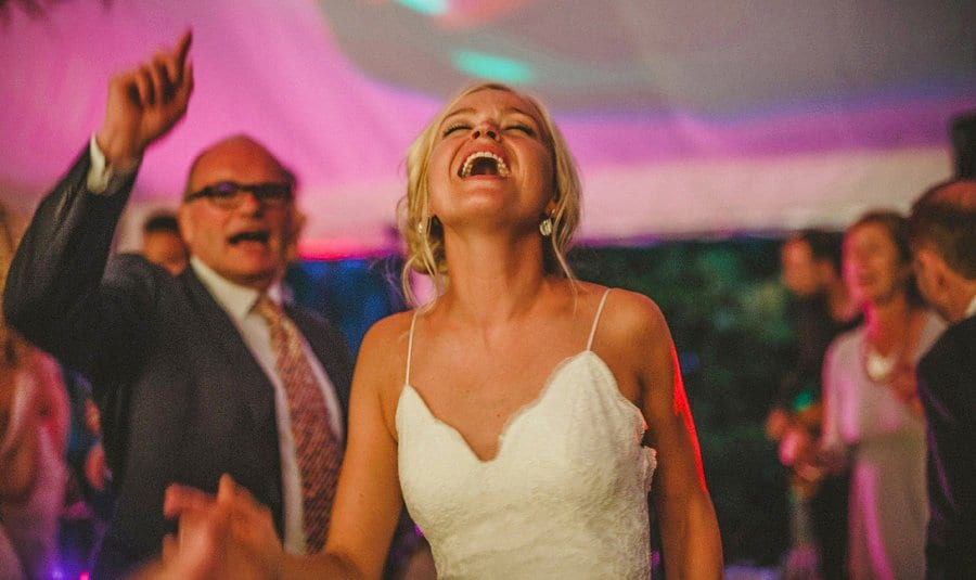 The bride closes her eyes and looks up as she dances in the marquee with friends and family