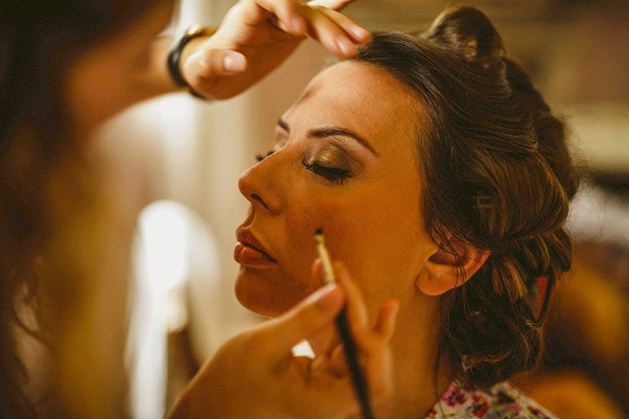 The make up artist applies eye liner to the brides eyelashes