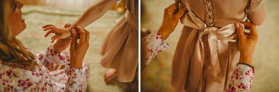 A bridesmaid fastens the ribbons to the back of the flower girls dress