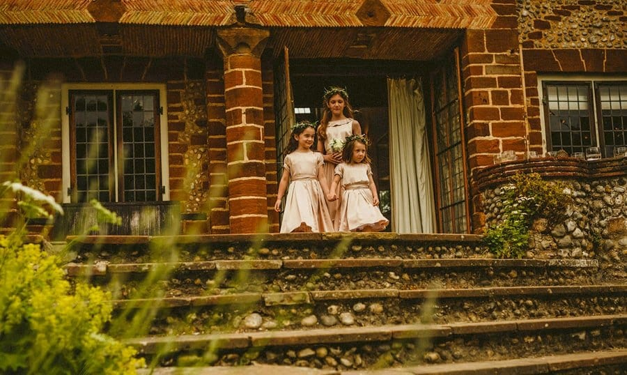 The flower girls leave the house and start to walk down the stone steps