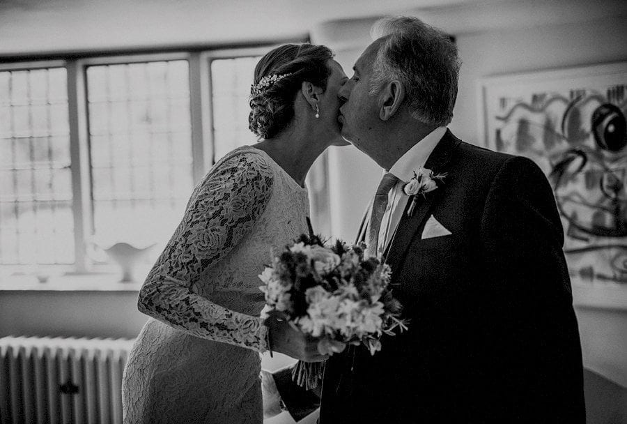The bride kisses her father before they leave for the outdoor ceremony at Voewood in Norfolk