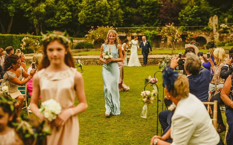 A bridesmaid and flower girls walk down the aisle of the outdoor ceremony at Voewood