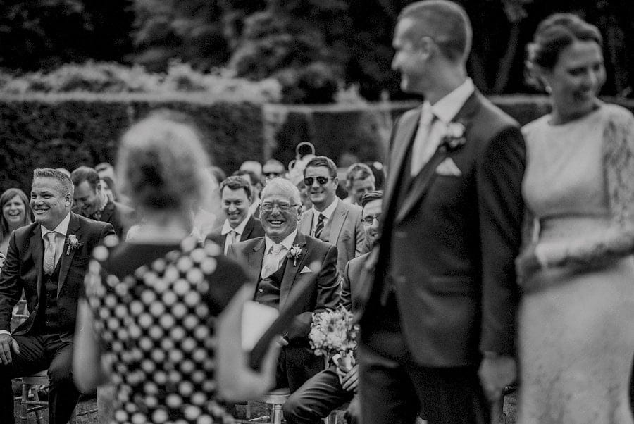 The grooms father and best man laugh during the outdoor wedding ceremony