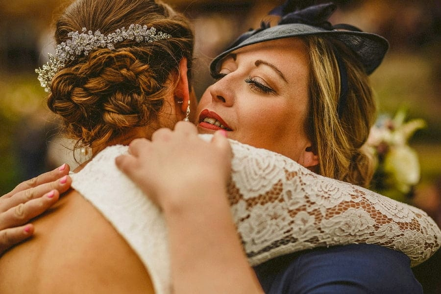 A wedding guest embraces the bride at the end of the outdoor wedding ceremony